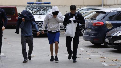 Uno de los cuatro detenidos, en el centro, por los atracos de los taxistas en Palma llega a los juzgados de Vía Alemania.