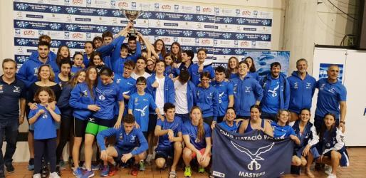 Los nadadores del Club Natación Palma alzan el trofeo de campeones.