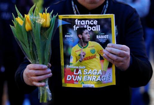 Un hombre sostiene una portada ilustrada con una fotografía de Emiliano Sala junto con unas flores en uno de los homenajes que se produjeron en Nantes, ciudad desde la que salió la avioneta de la que posteriormente se perdió la pista.