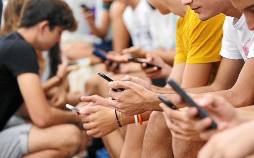 Imagen de archivo de menores de Balears manejando sus teléfonos móviles.