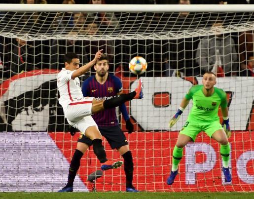 El delantero francés del Sevilla FC Wissam Ben Yedder (i) tira a puerta ante Gerard Piqué y el guardameta holandés Jasper Cillessen, ambos del FC Barcelona.