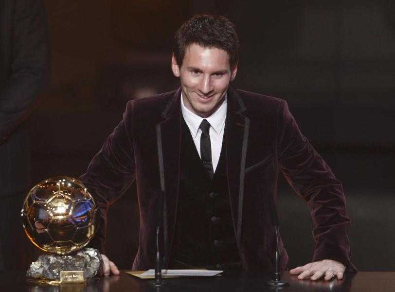 Messi of Argentina, FIFA World Player of the Year poses next to his FIFA Ballon d'Or 2011 trophy during the FIFA Ballon d'Or 201