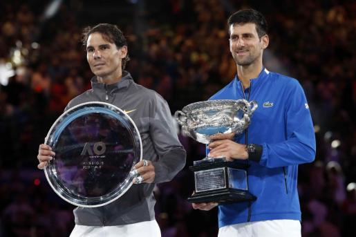Rafael Nadal y Novak Djokovic posan con sus trofeos tras la final del Open de Australia.