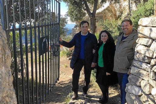 En los últimos años la cueva y el entorno han sido objeto de frecuentes actos de vandalismo. En la imagen el conseller Francesc Miralles, la directora insular Kika Coll y Jaume Lliteras, teniente de alcalde de Algaida, en la puerta que da acceso a la cueva. La restauración acaba en marzo.
