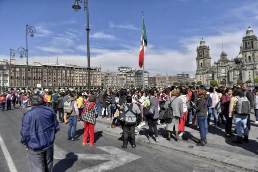 Cientos de personas evacuan los edificios en el zócalo de la capital de México tras un sismo de magnitud 6,5 que se produjo este viernes, en Ciudad de México.
