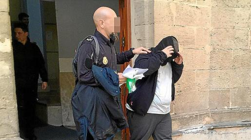 Samuel A., saliendo del juzgado custodiado por un policía nacional.