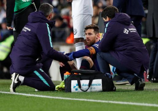 Lionel Messi es atendido por los médicos del Barça durante el partido contra el Valencia de este sábado.