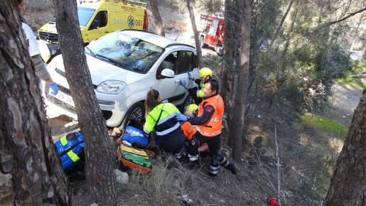 Los servicios de emergencias atienden a la herida, bajo su vehículo.