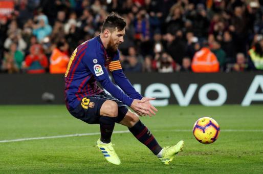 Leo Messi recoge el balón tras marcar su primer gol ante el Valencia.