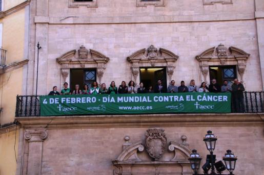 Autoridades municipales en el balcón de Cort con la pancarta alusiva al Día Mundial Contra el Cáncer.