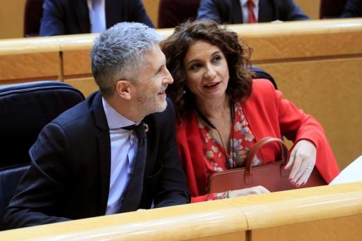 El ministro del Interior, Fernando Grande-Marlaska y la ministra de Hacienda, María Jesús Montero, conversan durante la sesión de control al Gobierno en el Pleno del Senado.