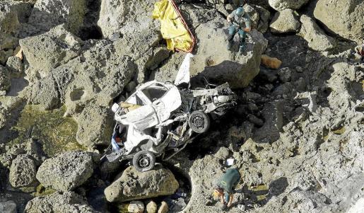 Dos guardias civiles inspeccionan el vehículo que el miércoles por la mañana se precipitó en Cabo Blanco. Un joven murió. Fotos: ALEJANDRO SEPÚLVEDA