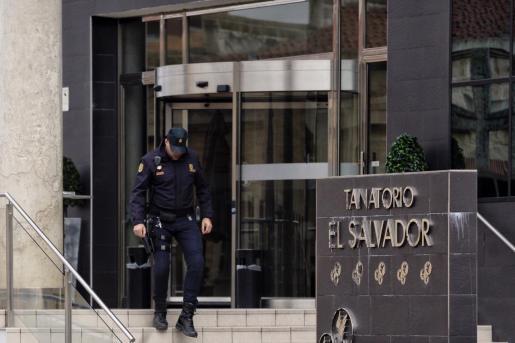 Un efectivo de la Policía Nacional sale del tanatorio El Salvador, en Valladolid.