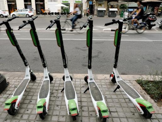 Imagen de archivo varios patinetes eléctricos aparcados en la acera.