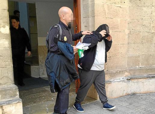 Un agente de la Policía Nacional, junto Samuel A., en los juzgados de Vía Alemania.