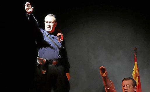 El candidato de Podemos, Yllanes, brazo en alto con pistola y correaje.