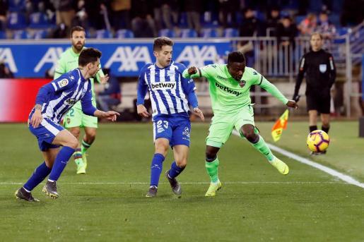 El delantero nigeriano del Levante Simon Moses (d) pelea un balón con el centrocampista del Deportivo Alaves, Jony Rodríguez (c).