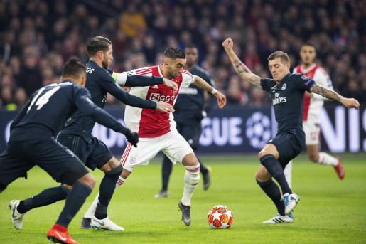 Hakim Ziyech (c) de Ajax Amsterdam en acción contra Sergio Ramos (2i) y Toni Kroos (d) del Real Madrid durante el partido de ida por los octavos de final de la Liga de Campeones.