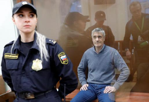 Michael Calvey custodiado por agentes de policía.