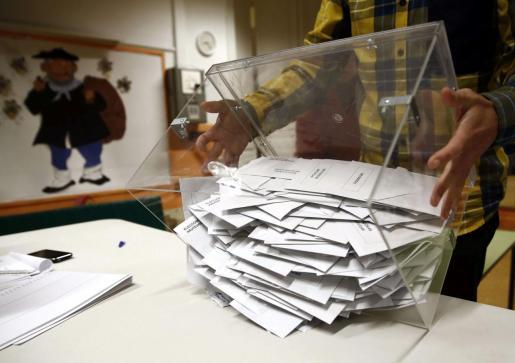 El presidente de una mesa electoral deposita los votos de la urna sobre una mesa para proceder a su recuento.
