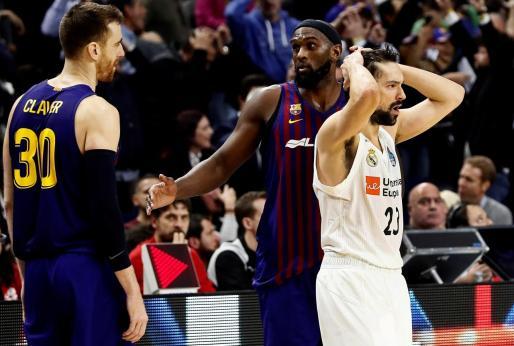 El jugador del Real Madrid Sergio Llull (d) y los del Barcelona Lassa, Víctor Claver (i) y Chris Singleton, durante la final de la Copa del Rey de baloncesto disputada en el WiZink Center, en Madrid.