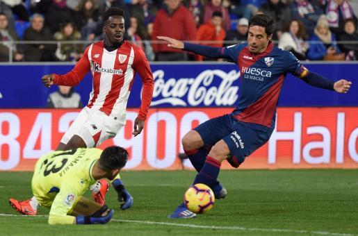 El delantero del Athletic de Bilbao Iñaki Williams (c) pelea un balón con Xabier Etxeita (d) y el portero Roberto Santamaría, ambos del Huesca.