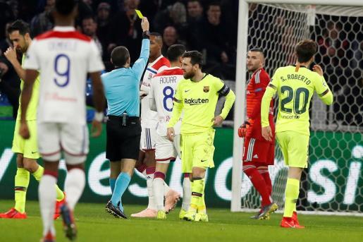 FR01. DECINES-CHAPIEU (FRANCIA), 19/02/2019.- El árbitro turco Cuneyt Cakir (c-i) muestra una tarjeta amarilla a Houssem Aouar (c-d) del Lyon durante el partido por los octavos de final de la Liga de Campeones de la UEFA entre el FC Barcelona y el Olympique de Lyon.