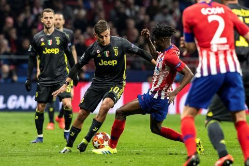 El delantero argentino del Juventus Paulo Dybala (2i) pelea un balón con el centrocampista ghanés del Atlético de Madrid Thomas Partey (2d).