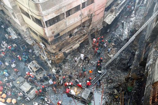 Varios bomberos inspeccionan los escombros tras el incendio declarado en el barrio Chawkbazar del casco viejo de Dacca (Bangladesh).