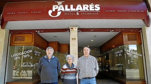 Antònia Ferrer, entre sus hijos, Juan y Gabriel Pallarés, frente al comercio, que llevaba abierto desde 1973.