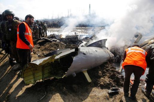 Miembros de la Fuerza Estatal de Respuesta ante Desastres inspeccionan los restos de un avión de combate que se estrelló este miércoles a unos 20 km de Srinagar.
