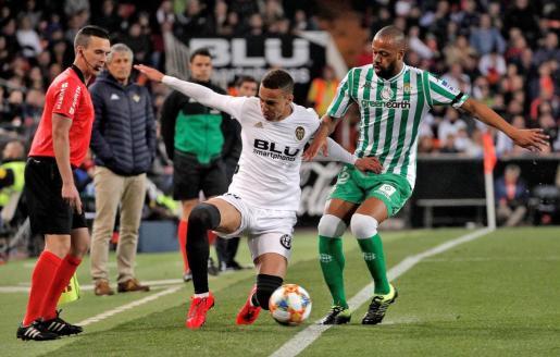 El delantero hispano brasileño del Valencia CF, Rodrigo Moreno, disputa un balón con el defensa brasileño del Real Betis, Sidnei Rechel Da Silva, en el partido de vuelta de las semifinales de la Copa del Rey.