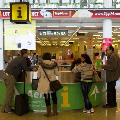 Un grupo de pasajeros consulta en el mostrador de AENA del aeropuerto de Son San Joan.