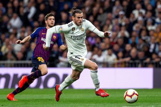 El delantero galés del Real Madrid Gareth Bale (d) se escapa de Sergi Roberto, del FC Barcelona, durante el partido de la 26ª jornada de Liga en Primera División entre el Real Madrid y el Barcelona.