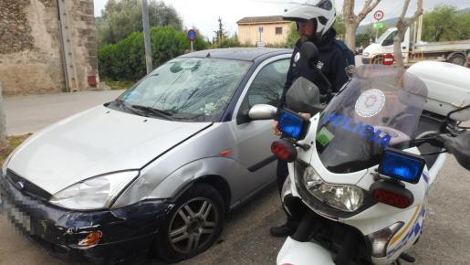 Un policía local con el coche que causó el accidente.