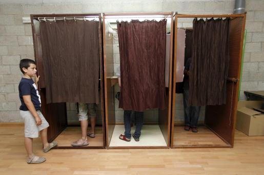 Electores eligiendo las papeletas en secreto.