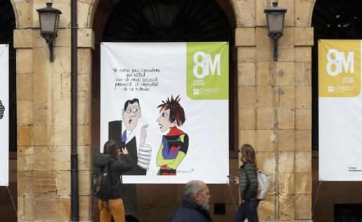 Vista del cartel institucional colgado en el Ayuntamiento de Oviedo con motivo del 8-M en el que se observa a un magistrado dirigiéndose a una mujer a la que advierte que «con su cruel belleza provoca la crueldad de su marido».