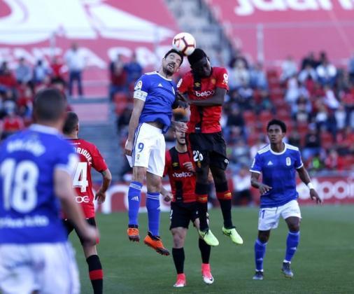 El malloquinista Baba y el oviedista Toché pugnan por un balón aéreo durante el partido disputado en Son Moix.