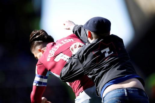 Un aficionado agrede a Jack Grealish, futbolista del Aston Villa, durante el derbi de Birmingham.