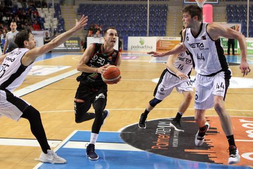 Álex Hernández intenta penetrar a canasta ante la defensa de Huertas y Lammers.