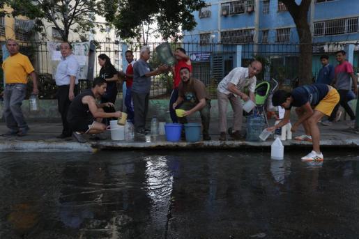 Un grupo de personas intenta recolectar agua en el sistema de alcantarillado.