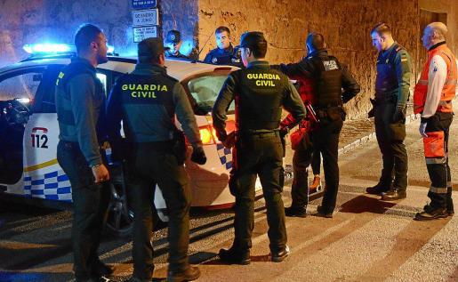 Policías locales, guardias civiles y un sanitario junto al coche patrulla donde estaba el detenido.