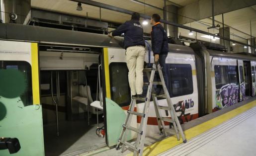 Operarios inspeccionando el vagón que se icendió en la estación de Palma.