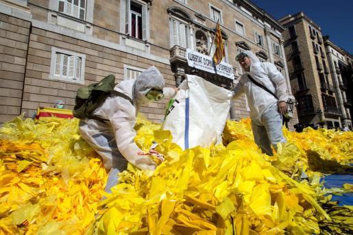Miembros de la brigada de limpieza d'Els Segadors del Maresme, que se dedican a quitar lazos amarillos de lugares públicos, los depositan frente a la fachada principal del Palau de la Generalitat.