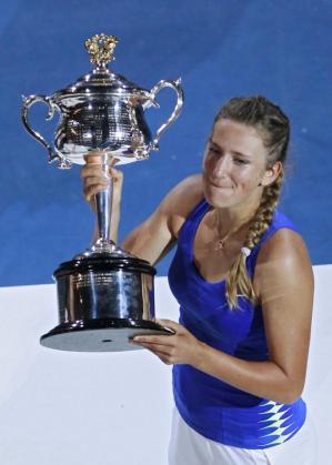 La tenista Victoria Azarenka sostiene el trofeo que la acredita como ganadora del Abierto de Australia.