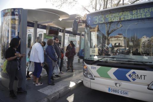Usuarios, en la parada, y un autobús de servicios mínimos.