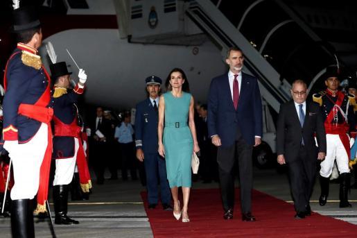 Los reyes de España Felipe VI (c) y Letizia (c.i) caminan en medio de una guardia de honor luego de ser recibidos por el ministro de Relaciones Exteriores de Argentina, Jorge Faurie (2d), tras aterrizar este domingo en el aeroparque metropolitano Jorge Newbery en Buenos Aires (Argentina).