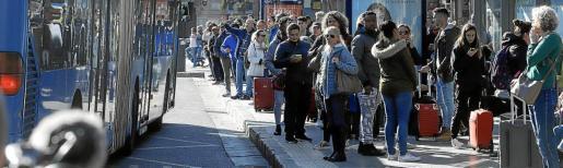 Pasajeros esperan para entrar en un autobús que ya estaba lleno en la plaza de España.