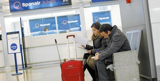 Afectados por el cierre de Spanair rellenan en el aeropuerto de Barajas un formulario para reclamar daños y perjuicios a la compañía aérea.