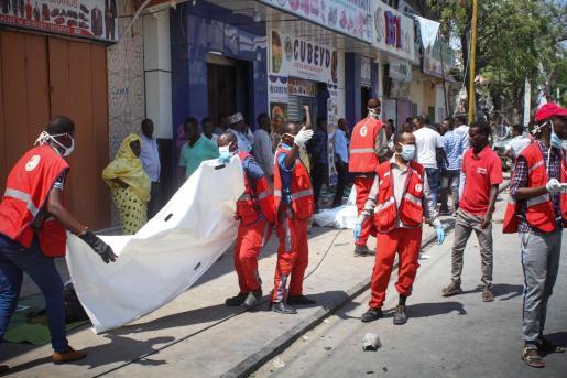 Médicos somalíes se disponen a trasladar el cadáver de una víctima tras la explosión de un coche bomba.